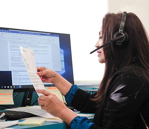A biller is working with insurance in front of her computer and documentation