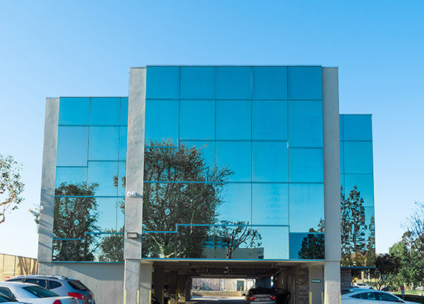 specialty glass building and bottom floor parking lot in a blue sky