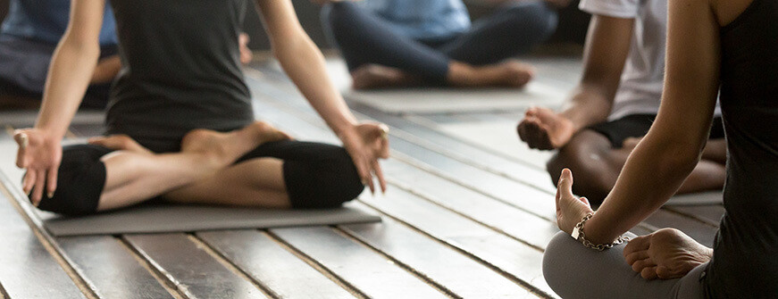 group people sitting in lotus position practicing yoga